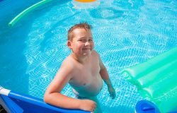 Мальчик в иметь потеху в бассейне стоковые изображения
