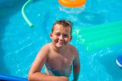 Мальчик в иметь потеху в бассейне стоковые фотографии rf