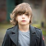 Мальчик в длинном пальто стоя в дворе фермы стоковые изображения rf