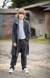 Мальчик в длинном пальто стоя в дворе фермы стоковые фотографии rf