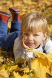мальчик в листьях лож осени Стоковая Фотография