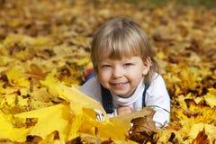 мальчик в листьях лож осени Стоковое фото RF