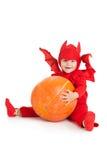 Мальчик в костюме красного дьявола сидя и держа большая тыква Стоковое Изображение RF