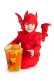 Мальчик в костюме красного дьявола сидя около большого ведра Стоковое фото RF