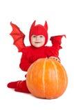 Мальчик в костюме красного дьявола сидя около большой тыквы Стоковое Изображение