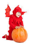 Мальчик в костюме красного дьявола сидя около большой тыквы Стоковая Фотография