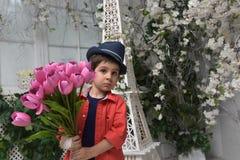 мальчик в красной рубашке и шляпе с букетом тюльпанов внутри Стоковая Фотография