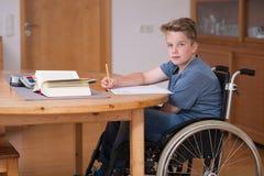 Мальчик в кресло-коляске делая домашнюю работу Стоковое Изображение