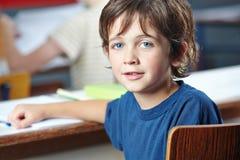 Мальчик в классе в начальной школе Стоковая Фотография