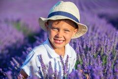 Мальчик в поле лета лаванды стоковое изображение