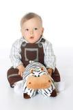 Мальчик в прозодеждах держа корову игрушки подушек Стоковая Фотография