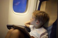 Мальчик в плоскости смотря вне иллюминатор с пусковой площадкой дальше стоковая фотография rf