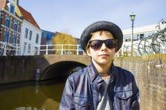 Мальчик в солнечных очках против предпосылки канала Стоковые Изображения