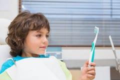 Мальчик в стуле дантистов держа toothrbrush Стоковое Изображение RF