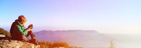 Мальчик в сценарных горах смотря конус сосны Стоковые Изображения
