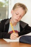 Мальчик в черном свитере делая домашнюю работу Стоковые Фото