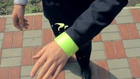 Мальчик в школьной форме положенной на себя и браслет рефлектора диапазона кнопки безопасности рефлектора девушки Жидкость механи сток-видео