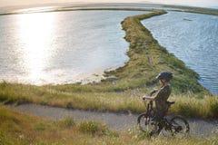 Мальчик в шлеме ехать его велосипед на заходе солнца Стоковые Фотографии RF