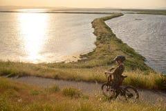 Мальчик в шлеме ехать его горный велосипед на заходе солнца Стоковые Фотографии RF