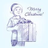 Мальчик в шляпе Санты держа руку подарка на рождество Стоковое фото RF