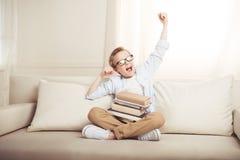Мальчик в eyeglasses сидя на софе при книги протягивая и зевая Стоковые Фото