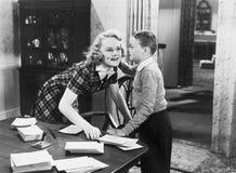 Мальчик говоря секрет к молодой женщине (все показанные люди более длинные живущие и никакое имущество не существует Гарантии пос стоковое изображение