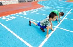 Мальчик готовый для того чтобы начать на беговой дорожке Стоковое фото RF
