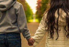 Мальчик & девушка держа руки смотря на путь для того чтобы дистанцировать Стоковые Фото