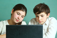 Мальчик девушки с компьтер-книжкой изучая онлайн урок Стоковые Фото