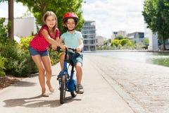 Мальчик девушки уча для того чтобы ехать велосипед на пути цикла Стоковые Фото