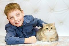 Мальчик лежа вниз и усмехаясь Котенок великобританской сини Shorthair Стоковое Изображение
