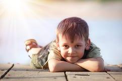 Мальчик лежа на деревянной платформе стоковое изображение rf