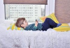 мальчик лежа на окне Стоковое Изображение