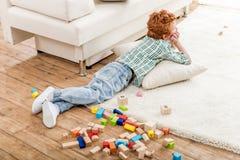 Мальчик лежа на подушке около красочных деревянных блоков разбросал на пол стоковая фотография rf