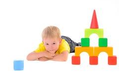 Мальчик лежа около здания игрушки покрашенных кубов Стоковые Изображения RF