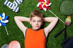 Мальчик лежа с оборудованием спорта на конце травы вверх стоковое изображение rf
