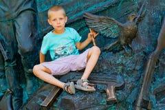 Мальчик держа голубя в его руках Стоковое Изображение