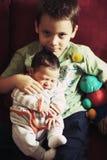 Мальчик держа его сестру Стоковые Изображения