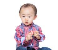 Мальчик держа деревянный блок игрушки и смотря в сторону стоковые изображения rf