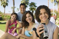 Мальчик (13-15) держа камкордер сидя outdoors с сестрой (7-9) и портретом родителей. Стоковое Фото