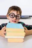 Мальчик держа книги на таблице в классе Стоковая Фотография RF