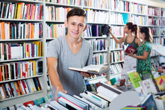 Мальчик держа книгу и смотреть стоковая фотография rf