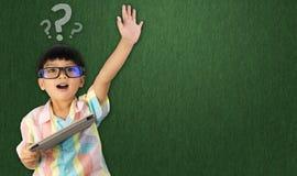 Мальчик держа повышение таблетки его рука вверх для вопроса стоковые изображения