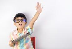 Мальчик держа повышение таблетки его рука вверх стоковые изображения