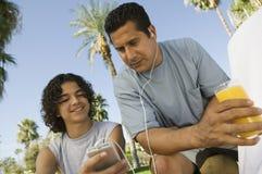 Мальчик (13-15) держа портативного отца аудиоплейера слушая с наушниками и держа стекло сока. Стоковые Фото