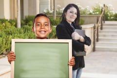 Мальчик держа пустую доску мела на кампусе с учителем позади Стоковое Изображение RF