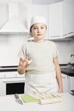 Мальчик держа сырцовый круассан стоковое фото rf