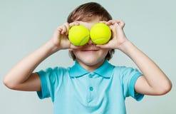 Мальчик держа теннисные мячи вместо глаз, усмехаясь Стоковые Изображения