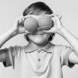 Мальчик держа теннисные мячи вместо глаз, усмехаясь Стоковое Изображение
