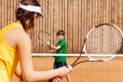 Мальчик держа теннисный мяч и ракетку, начиная комплект Стоковые Изображения RF